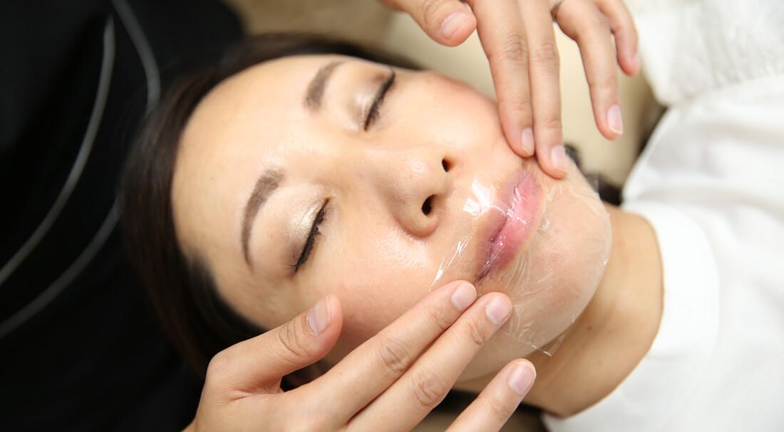 唇の乾燥にリップエステをする女性
